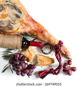 Leg of spanish serrano ham,  bread, wine and grapes isolated on a white background