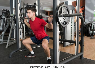 Leg training in gym, young man  squats exercising in gym club.