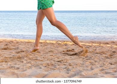 Leg of woman running on sand beach. summer vacation. Happy beautiful woman running on the beach.
