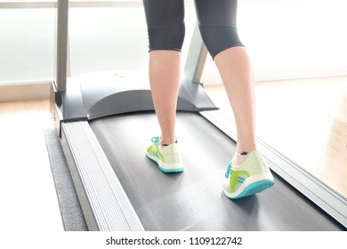 leg of woman running on treadmill in the gym which runner athletic by running shoes. Health and sport concept background,