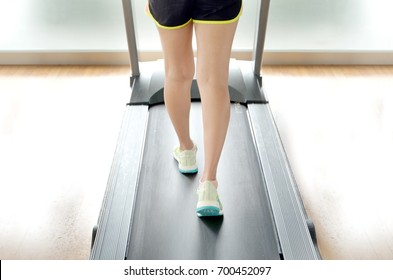 leg of woman running on treadmill in the gym which runner athletic by running shoes. Health and sport concept background soft focus