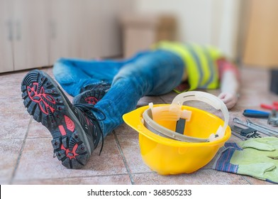 Leg and yellow helmet of injured lying worker at work.