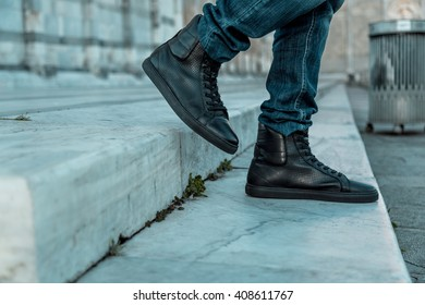 Leg of a Young Man with Blue Jeans and Black Shoes is descending from two Marbles Stairs. Shallow Deep of Field.