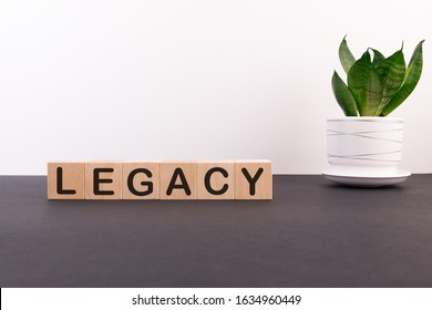 Legacy word on wooden cubes on a dark table with a flower and a light background