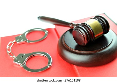 Legal concept with gavel and handcuffs against red background