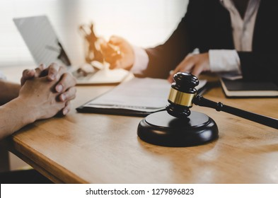 legal consultants, notary or justice lawyer discussing contract document with laptop computer wooden judge gavel on desk in courtroom office, business, justice law, insurance and legal service concept