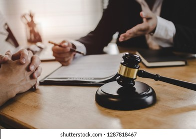 legal consultants, notary or justice lawyer discussing contract document with customer and wooden judge gavel on desk in courtroom office, business, justice law, insurance and legal service concept