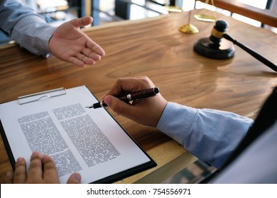 Legal counsel presents to the client a signed contract with gavel and legal law. justice and lawyer concept