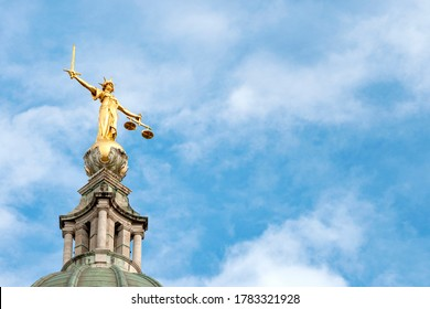 Legal  court, rule of law and criminal courtroom concept with photograph of golden Old Bailey statue of lady justice holding a balance scale and sword against the blue sky and clouds with copy space