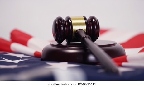 Legal gavel from a court room sitting on top of an American flag isolated on a white background