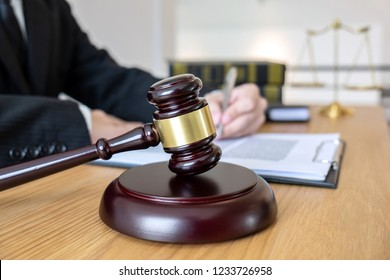 Legal law, advice and justice concept, male lawyer or notary working on a documents and report of the important case and wooden gavel, balance on table in courtroom.