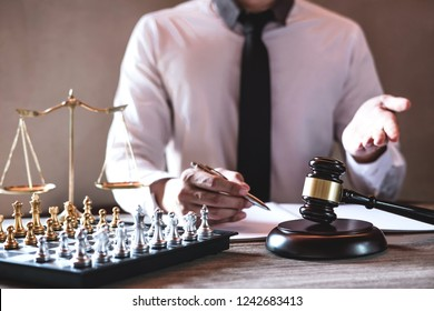 Legal law, advice and justice concept, Professional male lawyers working on courtroom sitting at the table and signing papers with gavel and Scales of justice.