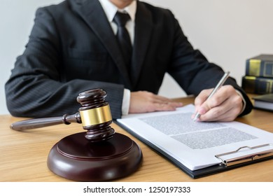 Legal law, advice and justice concept, male counseling lawyer or notary working on a documents and contract papers of the important case and wooden gavel, brass scale in courtroom.