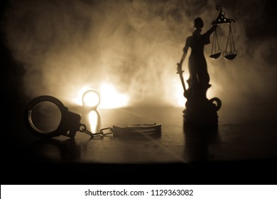 Legal law concept. Silhouette of handcuffs with The Statue of Justice on backside with the flashing red and blue police lights at foggy background. Selective focus