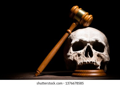 Legal law, justice and murderment concept. Wooden judge gavel hammer on human skull against black background. Free space.