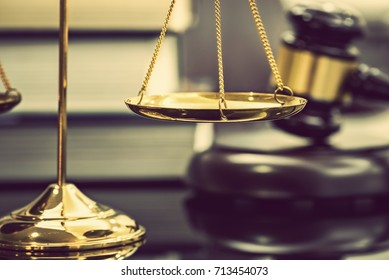 Legal office of lawyers, justice and law concept : Brass scales of justice with blurred wooden judge gavel or wood hammer and a soundboard on  judiciary desk in a courtroom with thick law books behind