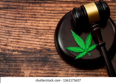 Legal weed, decriminalized pot or felony conviction for possession of a schedule one drug concept theme with a marijuana leaf and a wooden gavel isolated on wood background with copy space