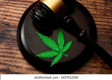 Legal weed, decriminalized pot or felony conviction for possession of a schedule one drug concept theme with a marijuana leaf and a wooden gavel isolated on wood background