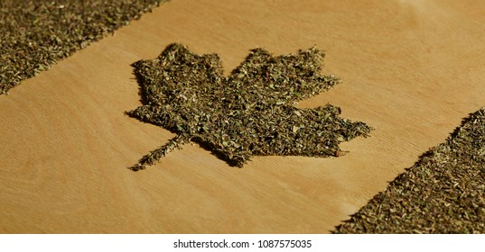 Legalization of cannabis for casual use in Canada. Thenational Canadian flag made of dry weed against the brown wooden background, angle view.  The image symbolizing the country's legal pot laws.