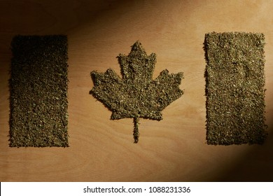 Legalization of cannabis for recreational use in Canada. The national Canadian flag made of dry weed against the brown wooden background.  The image symbolizing the country's legal marijuana laws.