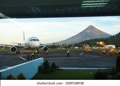 Legazpi Airport, Bicol -  Philippines - November 28, 2016: Service crew for a Cebu Pacific airplane flight works under threat of Mount Mayon Volcano, the country's most active.