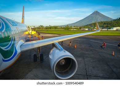Legazpi Airport, Bicol -  Philippines - November 28, 2016: Passengers and tourists board a Cebu Pacific Flight to Manila, With a Sunny View of Mt. Mayon Volcano in the Background.