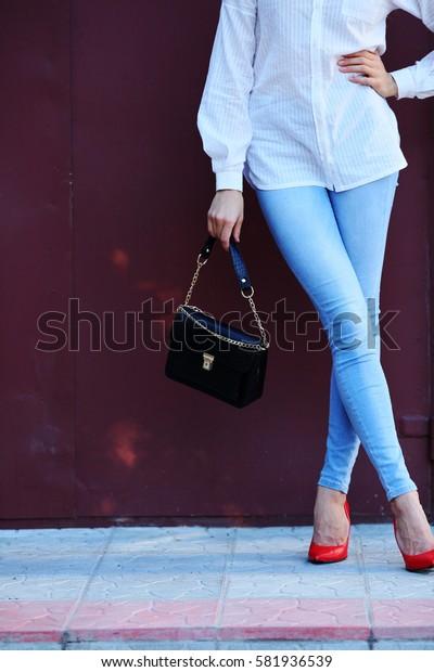 Leggy girl holding handbag in red shoes