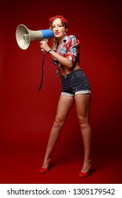 Leggy pretty young girl in shorts, red high heels, red bandana and decolletage colorful shirt holds megafone posing against red background. Full-growth retro-style pin-up portrait