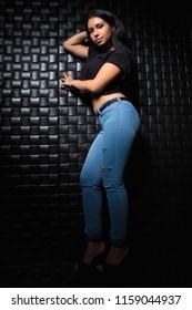 Leggy young brunette posing near a black wall