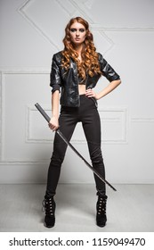 Leggy young woman wearing black clothes posing with steel sword