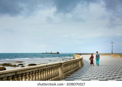 LEGHORN, ITALY - OCTOBER 3, 2017: Couple walks on Mascagni picturesque seashore terrace in Livorno, Tuscany.