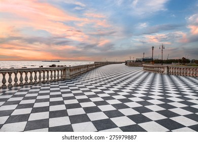 Leghorn (Livorno), Tuscany, Italy:  promenade Mascagni Terrace at sunset, a picturesque seashore on the Ligurian sea with black and white checkered pavement and columned bannister