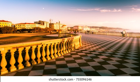 Leghorn (Livorno), Tuscany, Italy: promenade Mascagni Terrace at night, an elegant square on the coast with black and white checkered floor, columned bannister viewed against setting sun