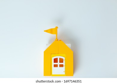 Lego house, stay home stay safe. Yellow toy house with lego family. Self-isolation during virus. Home office with family.