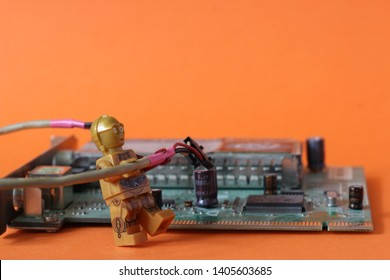 Lego mini figure of C3PO robor from Star Wars fixing the processor on some hi tech gadget. Technology repair and support concept. Editorial image, close up photo isolated on orange background.