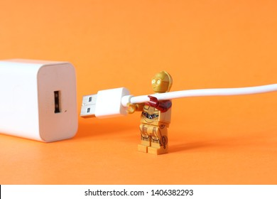 Lego mini figure of C3PO robot from Star Wars film series attaching type C USB cable to charger. Speed charging of mobile phones and repairing of broken cables and chargers. Editorial image, close up.