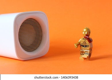 Lego mini figure of C3PO from Star Wars film series dancing to music from large, white speaker. Editorial image, close up photo isolated on orange background, macro photography, studio shot.