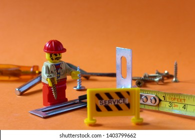 Lego mini figure man in civil engineer uniform with helmet working on building up something with tools with sign captioned SERVICE. Editorial image, close up photo isolated on orange background.