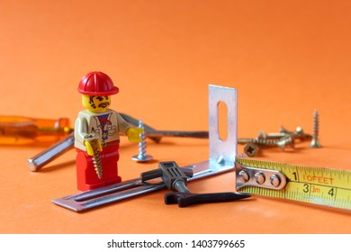 Lego mini figure man in civil engineer uniform with helmet working on building up something with tools. Editorial image, close up photo isolated on orange background, macro photography.