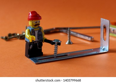 Lego mini figure man in handyman - service worker uniform working on building up something with tools. Editorial image, close up photo isolated on orange background, macro photography.