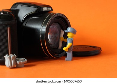 Lego mini figure of man in janitor uniform cleaning lense on camera. Editorial image, close up photo isolated on orange background, macro photography, concept of people doing their job.