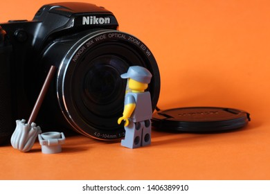 Lego mini figure of man in janitor uniform cleaning lense on photo camera with bucket and mop next to him. Editorial image, close up photo isolated on orange background, macro photography, close up.