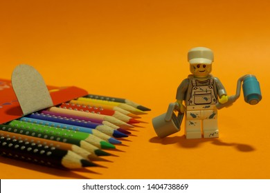 Lego mini figure man in painters uniform with his tools walking by a line of crayons. Artistic painting - drawing concept. Editorial image, close up photo, studio shot isolated on orange background.