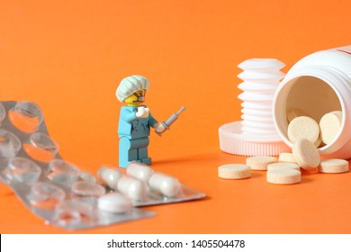 Lego mini figure of man in surgeon doctor uniform with hat and injection surounded by drugs in form of pills and tablets. Editorial image, close up photo isolated on orange background medicine concept