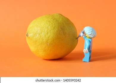 Lego mini figure of man in surgeon doctor uniform with hat and needle injecting chemicals into food. Editorial image, close up photo isolated on orange background. GMO and healthy organic concepts.