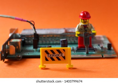 Lego mini figure man in working uniform with red helmet drilling something on hi tech computer part to repair it. Technology concept, editorial photo, close up image isolated on orange background.