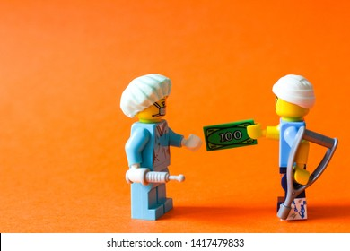 Lego mini figures of doctor in surgeon uniform and patient with broken leg and head giving money (bribe) to doctor. Editorial image, close up photo isolated on orange background, macro photography.