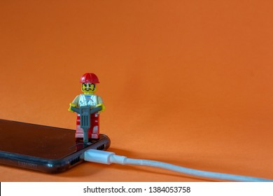 Lego minifigure man in handyman uniform fixing problems with broken mobile phone attached to charger. Editorial image, macro photography, close up photo, studio shot isolated on orange background.