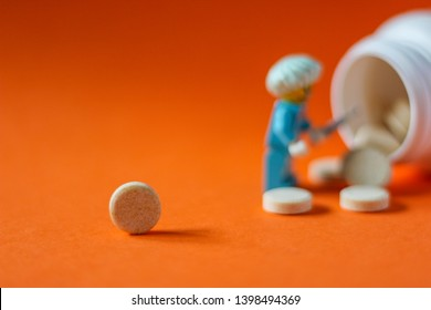 Lego minifigure of man in surgery doctor uniform next to bottle of spillled pills and tablets isolated on orange background. Editorial image, close up photo, studio shot, macro photography.