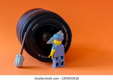 Lego minifigure showing cleaner cleaning photography lens with rug. Editorial image, close up photo, studio shot, macro photography, isolated on orange background.